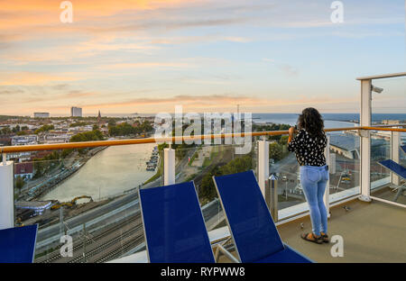 A woman on the upper deck of a cruise ship enjoys sunset over the coastal town, beach, Baltic Sea, Alter Strom canal and railway in Warnemunde Germany - Stock Image
