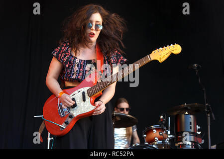 A musician playing a Fender Mustang guitar on stage at a music festival. The Mustang is a Made in Japan (MIJ) offset edition in red. The musician is Hannah Van Thompson of Scottish garage rock band The Van T's. - Stock Image