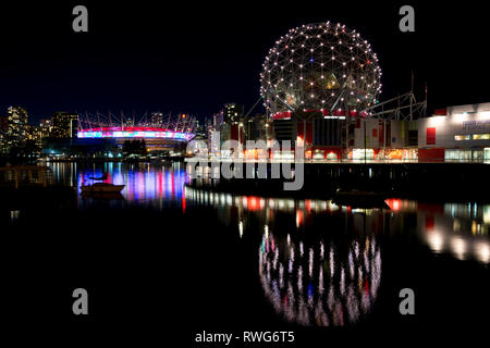 Telus World of Science in Vancouver, BC.  The geodesic dome of Science World Vancouver and BC Place stadium reflect on the waters of False Creek - Stock Image