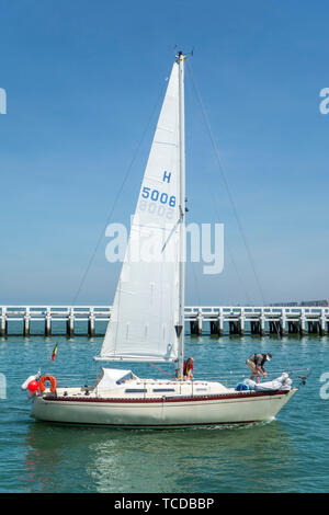 Sailboat / yacht sailing past the wooden jetty at Nieuport / Nieuwpoort, seaside resort along the North Sea coast, West Flanders, Belgium - Stock Image