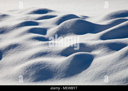 Wind blown snow forms a surrealist landscape - Stock Image