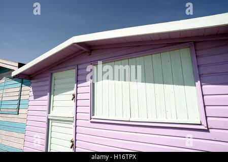 Pink painted wooden beach hut in summertime sunshine. - Stock Image