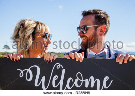 A man and a woman look at each other and smile over a wooden sign on which the word 'welcome' is written. - Stock Image