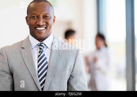 portrait of handsome African American businessman in office - Stock Image