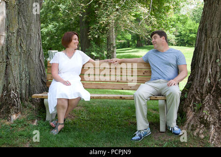 A happily married man and woman sit together on a park bench and look affectionately at one another - Stock Image