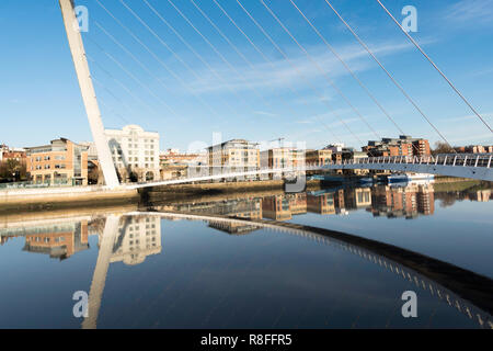 Buildings on Newcastle quayside framed by Gateshead Millennium bridge and reflected in the river Tyne, north east England, UK - Stock Image