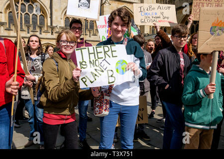Bath, Somerset, UK. 12th April, 2019.  Bath college students and school children carrying climate change placards and signs are pictured outside Bath Abbey as they take part in a climate change protest march through the centre of Bath. The pupils also walked out of school in February and March as part of a countrywide coordinated strike action to force action on climate change policy. Credit: Lynchpics/Alamy Live News - Stock Image