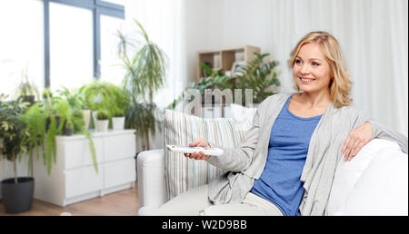woman with remote control watching tv at home - Stock Image