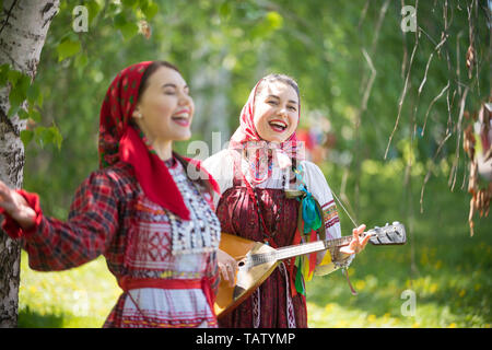 Two young attractive woman in traditional russian clothes singing in the forest. One of them playing balalaika - gorizontal shot - Stock Image