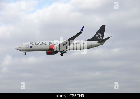 Star Alliance Scandinavian Airlines SAS Boeing 737-883 LN-RRL on approach to Heathrow : cloudy sky - Stock Image