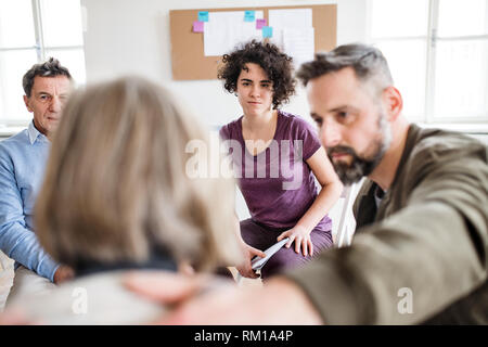 Men and women sitting in a circle during group therapy, supporting each other. - Stock Image