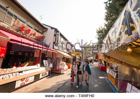 People walking past shops and food stalls along lane that leads to the Fushimi Inari Taisha Shinto shrine, Fukakusa Kaidocho, Fushimi Ward, Kyoto, Ho - Stock Image