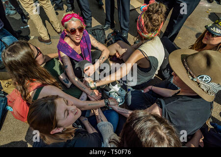 London, UK. 19th April 2019. People prepare to be arrested at Extinction Rebellion's Sea of Protest after police surrounded the yacht and put a ring of officers around Oxford Circus. Police tried to persuade protesters to leave by threatening them with arrest. Later there were a number of arrests of protesters who refused to leave. A few tried to get the large crowd to protect the yacht, but XR organisers persuaded them not to physically oppose the police action. Peter Marshall/Alamy Live News - Stock Image