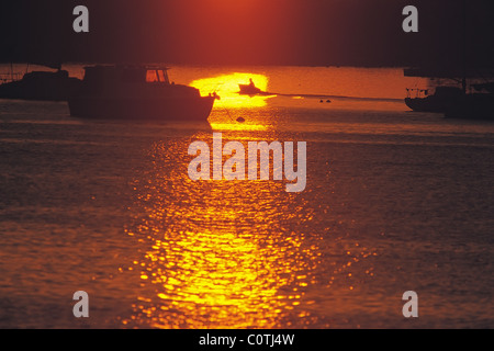 Solitary figure in dinghy silhouetted by sunrise - Stock Image