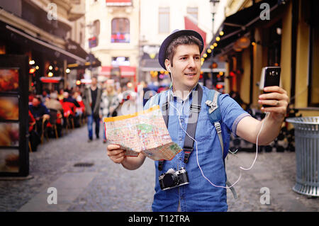 Young tourist man on streets of old town, having map, vintage photo camera and taking urban break selfie with his smart phone camera - Stock Image