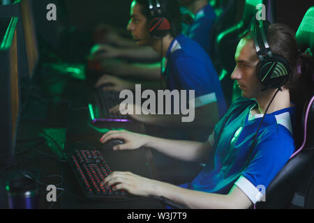 Young focused cyber gamer in headset sitting in gaming chair and using keyboard and mouse while playing video game during tournament - Stock Image