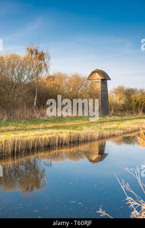 The Tower hide on the banks of Burwell Lode waterway on Wicken Fen nature reserve in warm evening sun, Cambridgeshire; England; UK - Stock Image