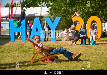 Children playing on Hay 30 sign with man sat in deckchair at Hay Festival 2017 Hay-on-Wye Powys Wales UK - Stock Image