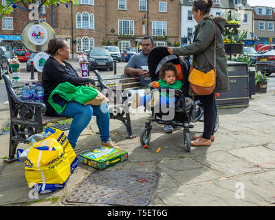 An ethnic South Asian family enjoying a break from shopping and resting in the Market Square in Thirsk North Yorkshire - Stock Image