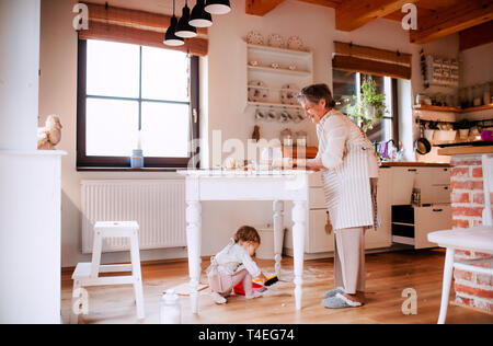 A senior great grandmother with small toddler grandchild making cakes at home. - Stock Image