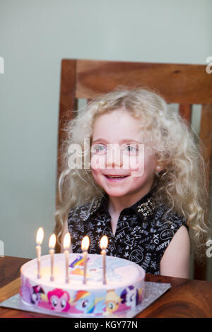 Girl smiling with candles on birthday cake - Stock Image