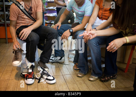Filipinos shop for shoes in a store at SM Glorietta Mall in Makati City, Metro Manila, Philippines. - Stock Image