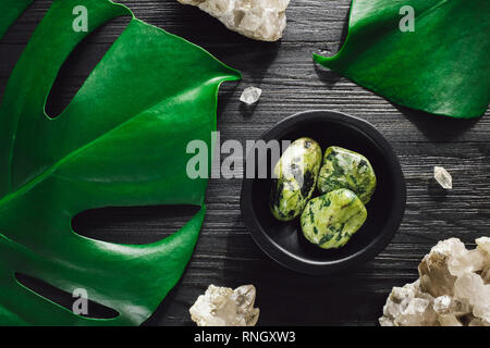 Nephrite Jade with Smoky Quartz and Monstera on Black Wood - Stock Image