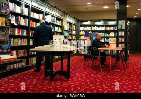 Two senior men in a bookshop one reading at a table and the other browsing the shelves - Stock Image
