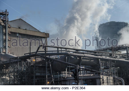 Recar steelworks:  Steam from quenching process at coke ovens rising behind pipes connecting to the blast furnace. - Stock Image