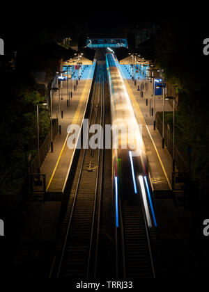 Winchester, England, UK - April 22, 2019: A South Western Railway passenger train calls at Winchester Railway Station in Hampshire at night. - Stock Image