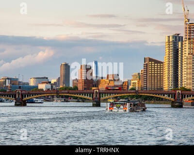 London, England, UK - May 28, 2019: A ferry boat passes under Vauxhall Bridge on the River Thames with the cityscape of Lambeth riverside behind. - Stock Image