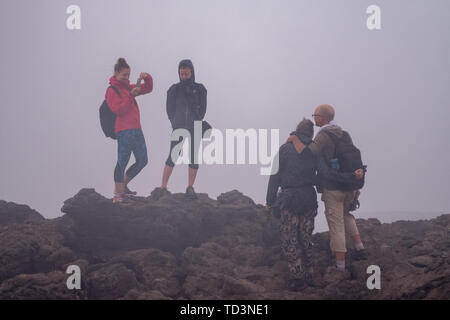 Tourists taking photographs at the Erta Ale Volcano, a continuously active basaltic shield volcano and lava lake in the Afar Region of Ethiopia - Stock Image
