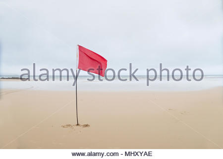 Red Danger Flag Flying On Beach In Cornwall - Stock Image