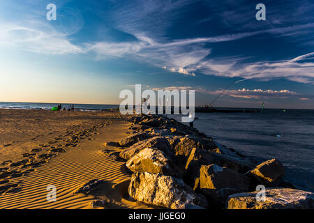 Fishermen standing on the stones separating the sea from the beach. Sunrise time. Jesolo, Italy. - Stock Image