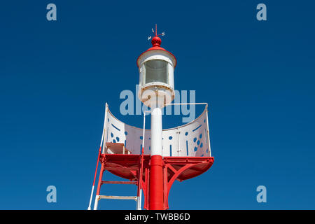 red and white navigation mark against a blue sky - Stock Image