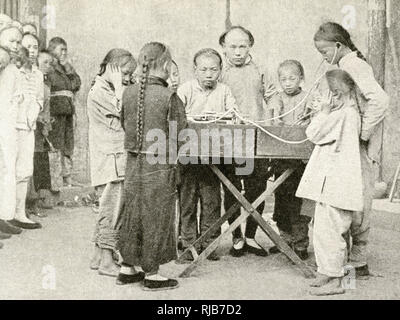 Schoolchildren listening to a recording on a gramophone, China, East Asia. - Stock Image