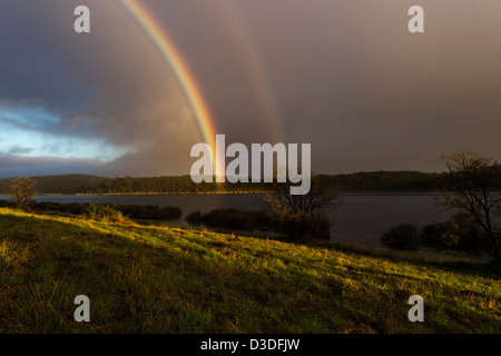 Rainbow over dam, QLD Australia - Stock Image