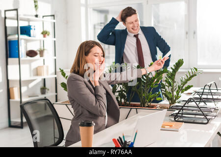happy businesswoman touching face whle holding smartphone and laughing with coworker in office - Stock Image