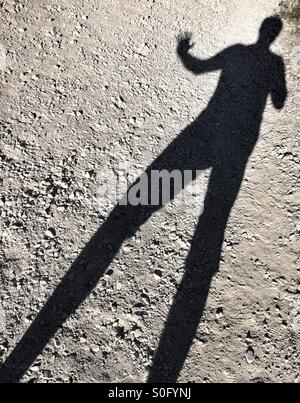 Shadow of a man with real long legs, waving. - Stock Image