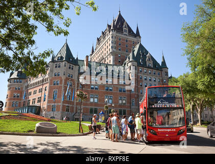 Group of tourists boarding a tour bus in front of the Chateau Frontenac in Old Quebec City, Province of Quebec, Canada - Stock Image