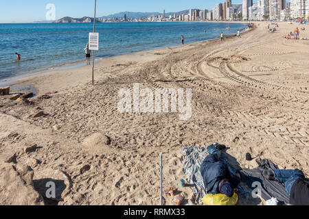 Rough sleepers on Levante beach in Benidorm amongst the holidaymakers just before Christmas - Stock Image