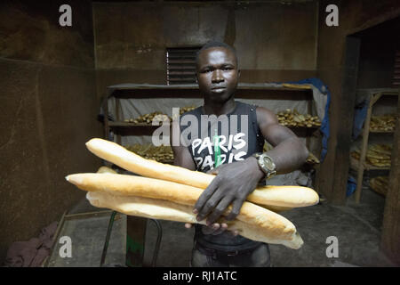 Yako, Burkina Faso; Baker with fresh loaves. - Stock Image