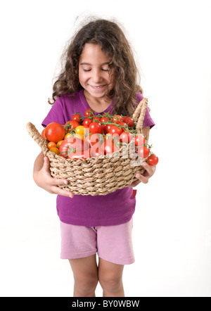 girl holdin a basket of tomatoes isolated on white - Stock Image
