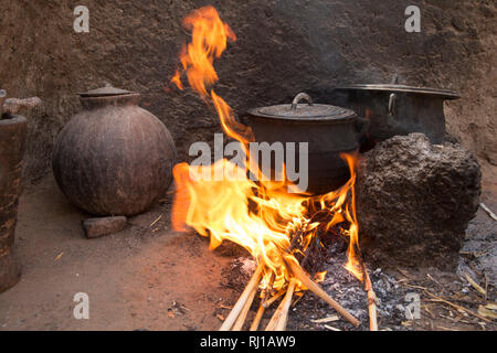 Kourono village, Yako province, Burkina Faso; Elizabeth Toro, 36 cooking the first meal of the day on an open fire in her kitchen. - Stock Image