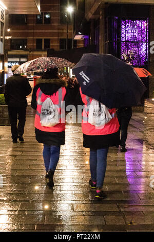 Leeds, UK. 5 October 2018.  Volunteer marshals at the Night Light festival in Leeds using umbrellas to keep dry during a wet and cold friday night. Credit: James Copeland/Alamy Live News - Stock Image