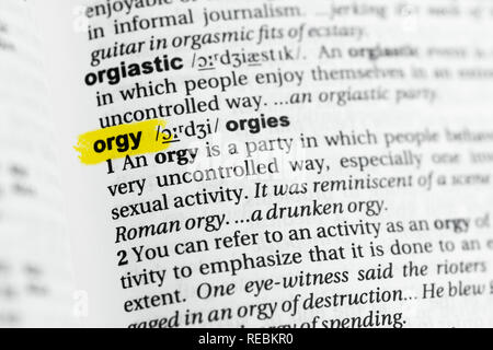 Highlighted English word 'orgy' and its definition at the dictionary. - Stock Image