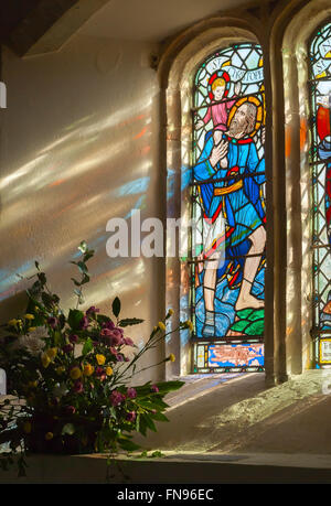 Stained glass panel and transmitted light reflections from St Nicholas Church West Itchenor West Sussex UK - Stock Image