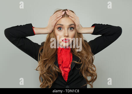 Shocked woman holding her head in her hands - Stock Image