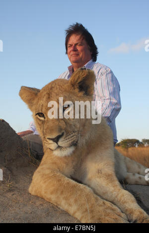 Man with young Lion against blue skies in the Africa savanna - Stock Image