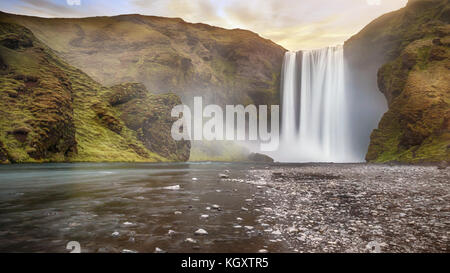 Long exposure of beautiful Skogafoss waterfall with spray over dramatic land. Pastel sky gives soft light. South - Stock Image